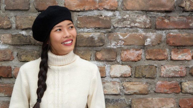Woman wearing a black beret leans against a brick wall.