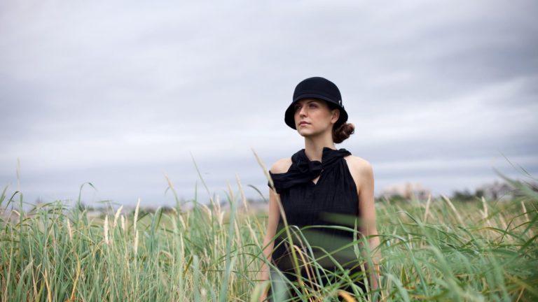 Woman wearing a black dress and black cloche hat in an open grassy field.