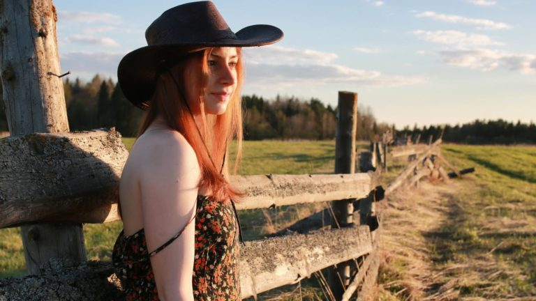A girl wearing a cowgirl hat leans against a wooden fence.