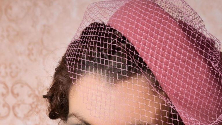 Woman wearing a pink pillbox hat.