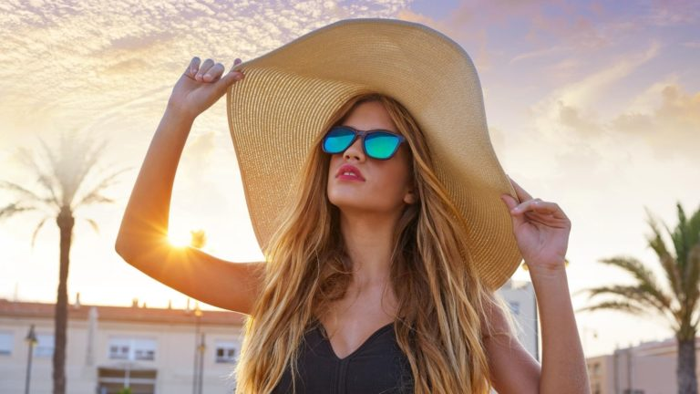 Lady wearing sun hat and sun glasses.