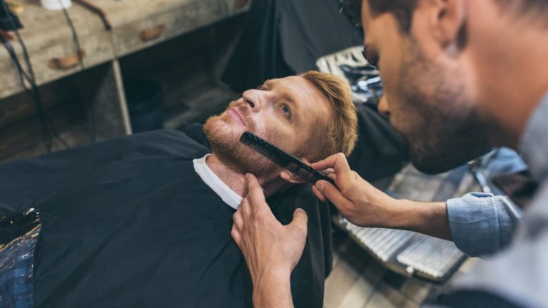 Barber styling a beard with a black barber comb.