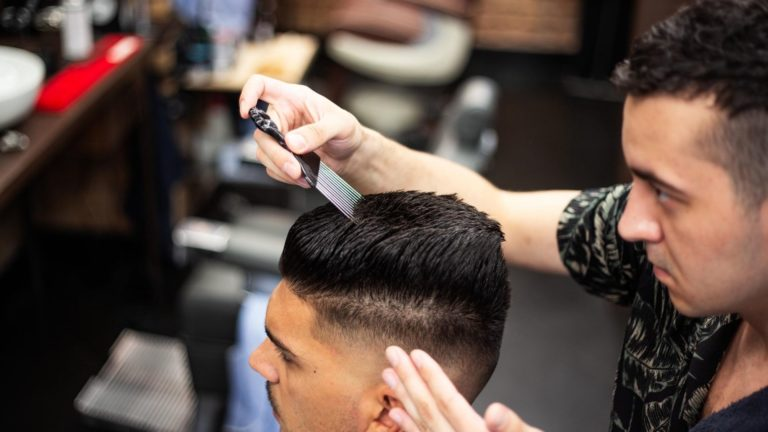 Barber using a pick comb to style hair.